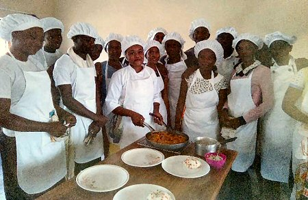 Charity Mweene (holding the pan) is teaching 25 sponsored students the art of catering