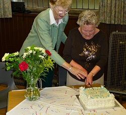 The Guild's 80th Birthday Cake cut by Mrs E. Craig, the longest serving member of over 60 years, and Sandra Marshall